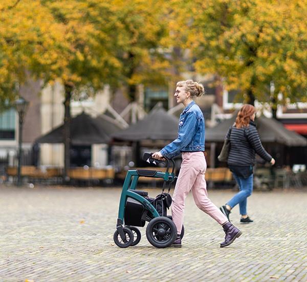 Blond meisje dat met een moderne rollator in het oude stadscentrum loopt