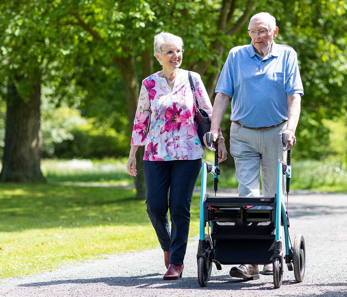 Man loopt met een blauwe Rollz Motion rollator en rolstoel in het park