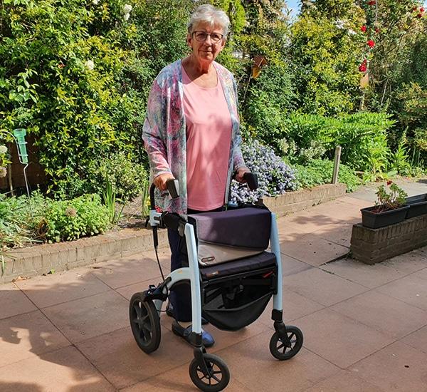 Vrouw gebruikt een rollator die is omgevormd tot een Parkinson rollator