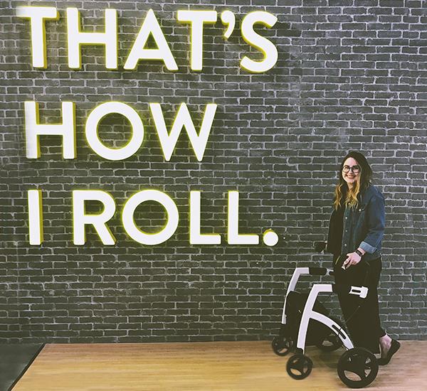 Gehandicapt meisje dat een Rollz Motion rollator en rolstoel in één gebruikt in het winkelcentrum